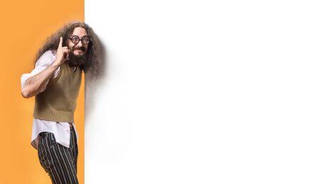 Foto de Freaky nerd pointing an empty billboard - Imagen libre de derechos