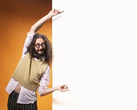 Foto de Funny nerd pointing on the white and empty commercial board - Imagen libre de derechos