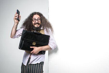 Foto de Portrait of a nerdy man holding a briefcase and a cell phone - Imagen libre de derechos