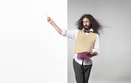 Foto de Skinny nerd pointing with a pen on the empty, commercial board - Imagen libre de derechos