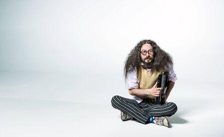 Foto de Portrait of a nerdy guy holding a briefcase and sitting on the white floor - Imagen libre de derechos