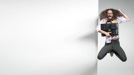 Foto de Portrait of a nerd jumping next to the white, commercial board - Imagen libre de derechos