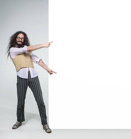 Foto de Eccentric guy pointing on the commercial, empty board - Imagen libre de derechos