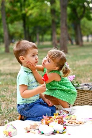 Photo pour Caucasian little boy and girl in the park - image libre de droit