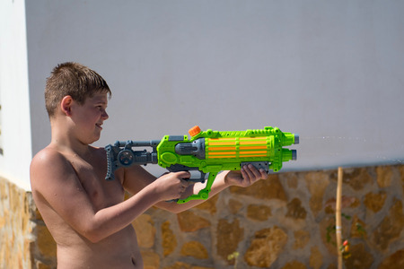 Photo for The boy play with water gun in the garden. - Royalty Free Image