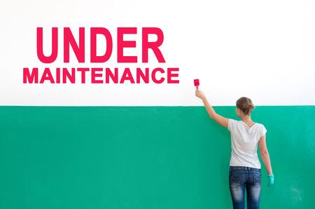 Photo pour On the white wall with paint write Under maintenance - image libre de droit