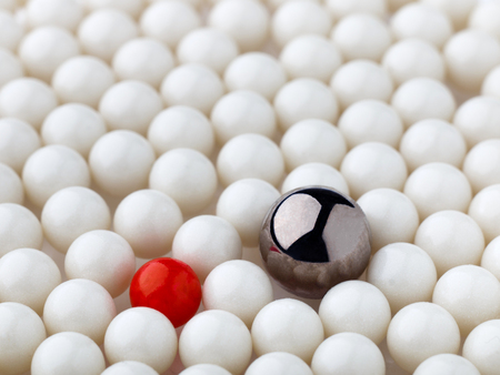 Photo pour stand out red and metal balls surrounded by white balls - image libre de droit