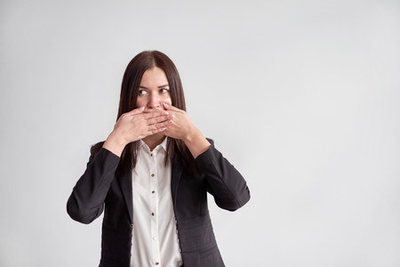 Photo pour woman in a suit, blocking her mouth, business compliance concept - image libre de droit
