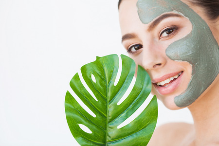 Skincare. Beautiful Woman With Perfect Skin Near Green Leaf Over White Background