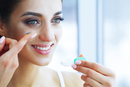 Foto de Health and Beauty. Beautiful Young Girl with Contact Lenses. Woman Holds Green Contact Lens on Her Finger. Healthy View. High Resolution - Imagen libre de derechos