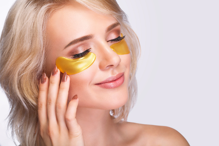 Foto de Patch Under Eyes. Beautiful Woman Face With Gold Hydrogel Patches, Lifting Anti-Wrinkle Collagen Mask On Fresh Healthy Facial Skin. High Resolution - Imagen libre de derechos