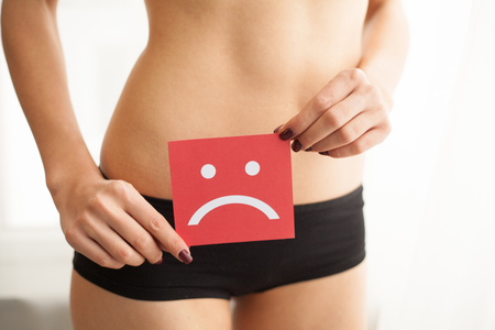 Foto de Vaginal or urinary infection and problems concept. Young woman holds paper with SOS above crotch - Imagen libre de derechos