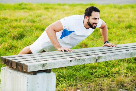 Foto per Portrait sporty man 30s in sportswear doing push-ups in green park - Immagine Royalty Free