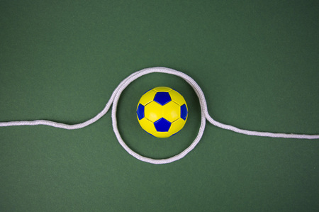 Photo for soccer ball on a green background, yellow-blue diamonds, with space for adding text - Royalty Free Image
