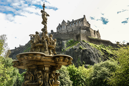 Foto de A view of Edinburgh Castle and fountain from the Princes Street gardens public park, Edinburgh, Scotland, United Kingdom - Imagen libre de derechos