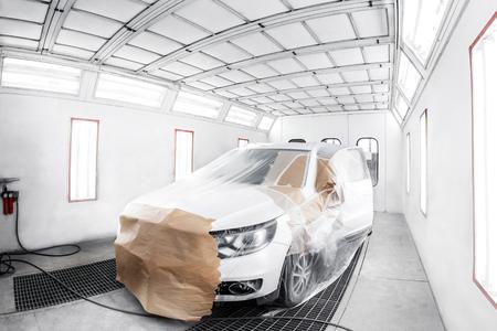 Foto de worker painting a white car in a special garage, wearing a costume and protective gear. - Imagen libre de derechos