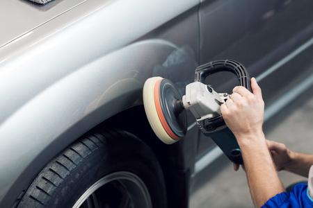 Foto de Close-up of hands worker using polisher to polish a gray car body in the workshop - Imagen libre de derechos