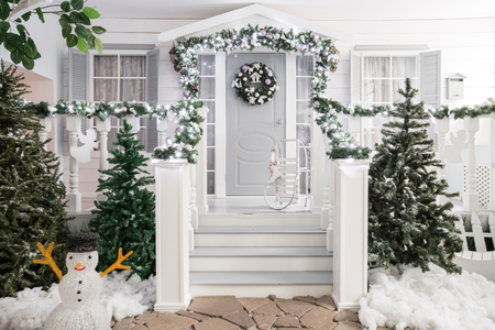 Foto de house entrance decorated for holidays. Christmas decoration. garland of fir tree branches and lights on the railing - Imagen libre de derechos