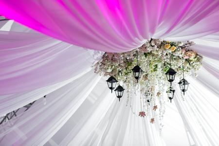 Photo pour Chandelier made of roses and white flowers hangs under the light tent. decorative lights - image libre de droit