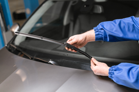 Photo pour Technician is changing windscreen wipers on a car station. - image libre de droit