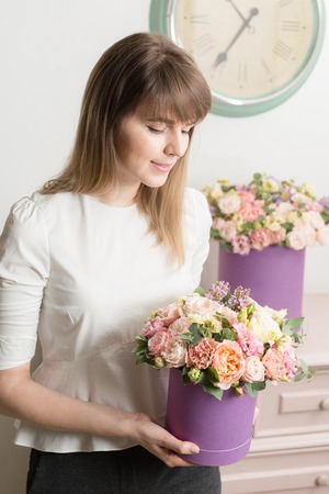 Photo for perfect gift or compliment. bouquet in lilac hatbox. beautiful luxury bunch of mixed flowers in womans hand. the work of the florist at a flower shop. - Royalty Free Image