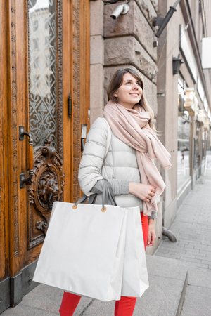 Photo pour Shopaholic beautiful happy woman goes shopping in the city. Young girl in red pants and a lot of grey paper bags her hands. The concept of shopping, sales and purchases of things. - image libre de droit