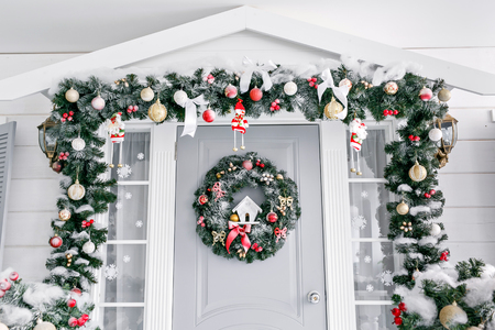 Foto de Christmas morning. house entrance decorated for holidays. Christmas decoration. garland of fir tree branches and lights on the railing - Imagen libre de derechos