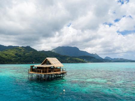 Foto de Overwater bungalow of black pearl farmers. Blue azure turquoise lagoon with corals. Emerald Raiatea island, Leeward / Society islands, French Polynesia, Oceania, South Pacific Ocean. - Imagen libre de derechos