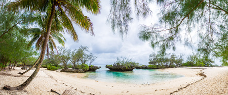 Foto de View of yellow white sandy tropical beach under palm trees in a secluded bay with coral rocks. Rimatara island, Austral / Tubuai islands, French Polynesia around Tahiti, Oceania, South Pacific Ocean. - Imagen libre de derechos
