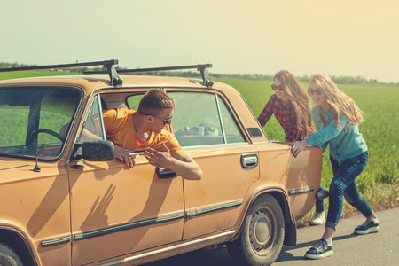 Photo for Young hipster friends on road trip on a summers day. Engine break down.Two girls pushing a vintage car while man is emboldening their.Travel, adventure, unforeseenteamwork, funny concept. Retro toned - Royalty Free Image