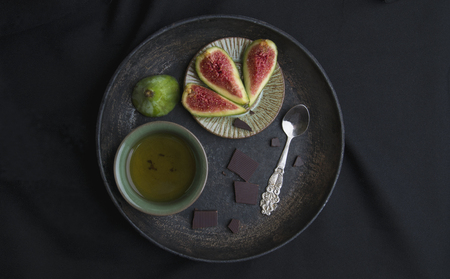 Photo for Cup of tea, chokolate, spoon on a black board - Royalty Free Image