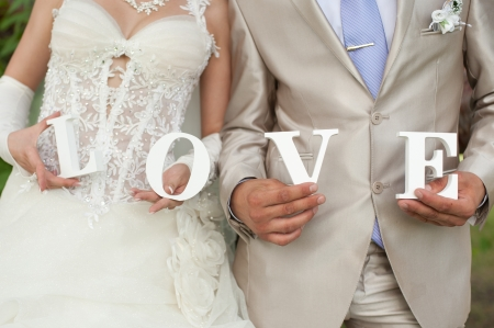 Photo for Closeup shot of bride and groom hands holding the word Love - Royalty Free Image