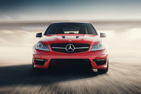Photo pour Saratov, Russia - August 24, 2014: Red Sport Car Mercedes-Benz C63 AMG Drive Speed On Asphalt Road At Sunset - image libre de droit