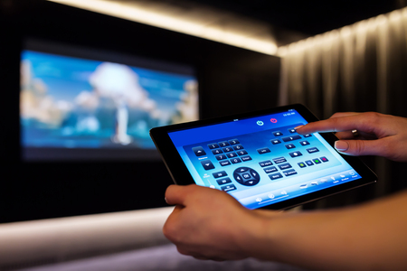 Foto de Woman is using tablet for remote control of home cinema theater - Imagen libre de derechos