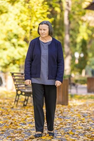 Foto de Depressed senior woman thinking worried outdoors in park. - Imagen libre de derechos