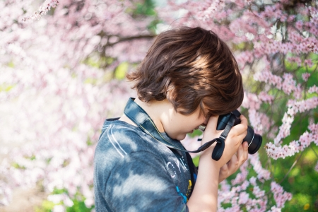 School-age boy with a camera photographs the cherry blossoms