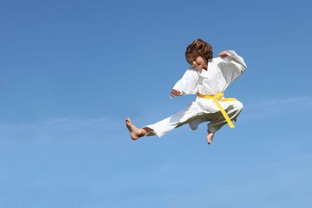 young boy doing karate kick