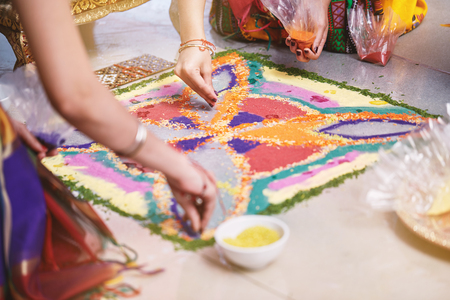 Photo pour Women helps coloring tradition colorful rice art or sand art (Rangoli) on the floor with paper pattern using dry rice and dry flour with colored from natural pigments like sindoor, haldi (turmeric) - image libre de droit