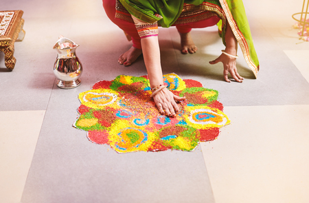Photo pour Women coloring tradition colorful rice art or sand art (Rangoli) on the floor with paper pattern using dry rice and dry flour with colored from natural pigments like sindoor, haldi (turmeric) - image libre de droit