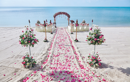Photo for Beach wedding venue setting on the white sand with beautiful panoramic ocean view background, Pink and red rose petals on the aisle - Royalty Free Image