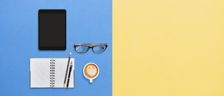 Foto de Modern office desktop flat lay working space lifestyle with tablet, notebook, pens, eyeglasses and a cup of hot coffee frothy drink on creativity color yellow blue background with copy space - Imagen libre de derechos