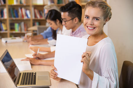 Positive young businesswoman or student holding sheet of paper and showing it at camera. Other people sitting in row behind her and working. Business or education concept