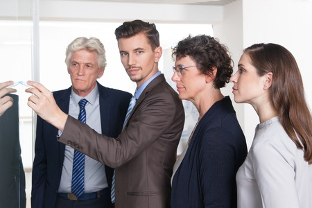Confident male manager drawing on glassy wall and looking at camera. Young businessman explaining business strategy. His colleagues listening to his idea. Teamwork or startup concept