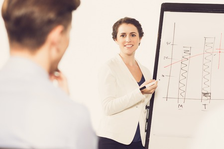 Smiling Businesswoman Presenting Chart to Audience