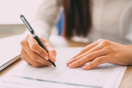 Photo for Hand of businesswoman or accountant checking financial document with ballpoint pen at table in office - Royalty Free Image