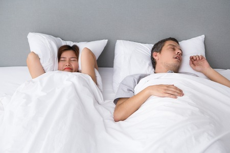 Photo pour Angry Asian woman annoyed with husbands snoring - image libre de droit
