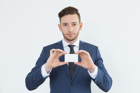 Foto de Serious confident young businessman showing card - Imagen libre de derechos