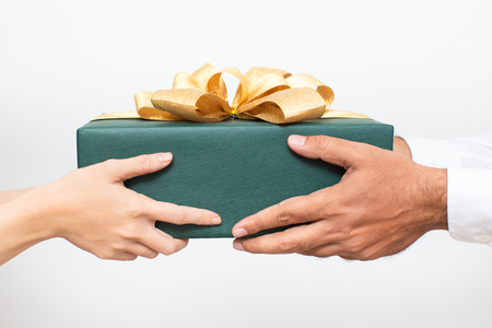 Photo pour Couple holding packaged Christmas present together - image libre de droit