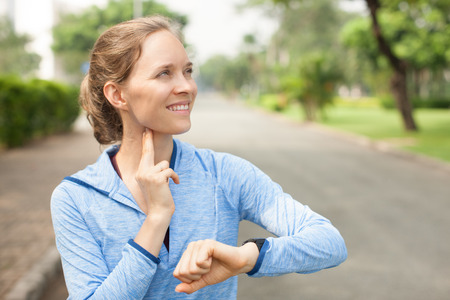 Foto de Smiling Sporty Woman Taking Pulse Outdoors - Imagen libre de derechos