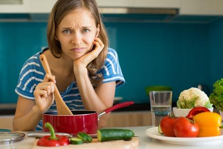 Foto de Dissatisfied Woman Cooking Dish in Sauce Pan - Imagen libre de derechos